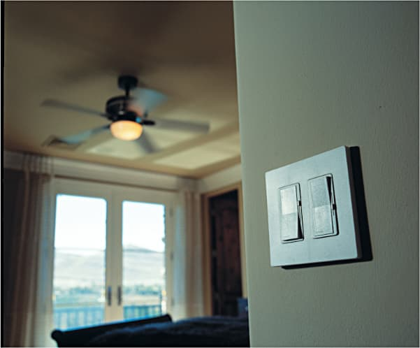 Dimmer switches on the wall with a fan light in the background
