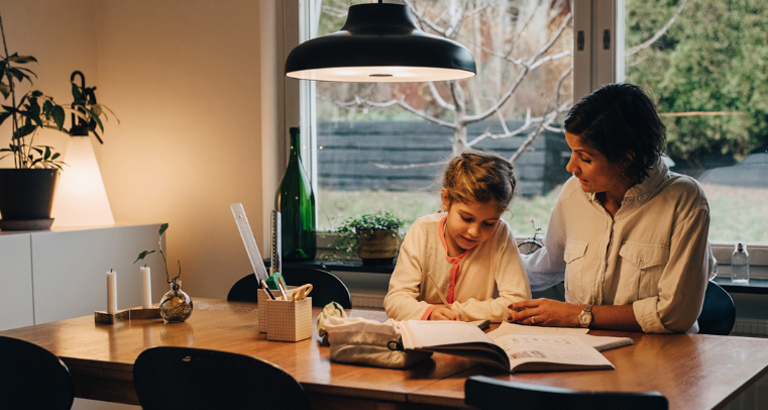 A mother and daughter sitting at the kitchen table doing homework