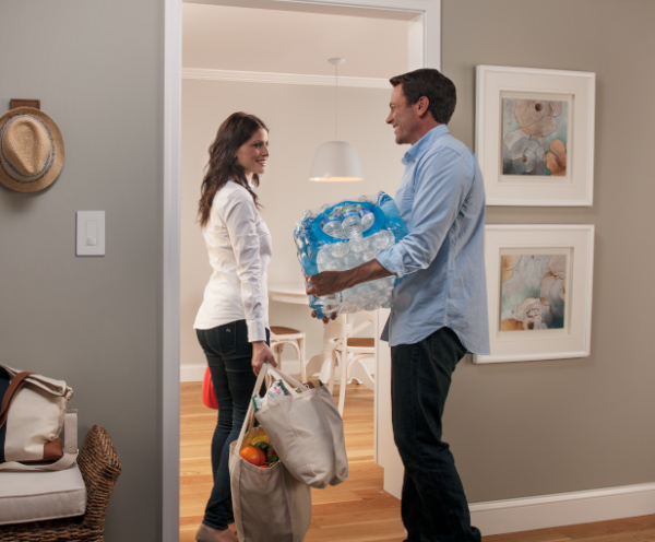 Husband holding a case of bottled water and wife holding two grocery bags in the doorway to their kitchen