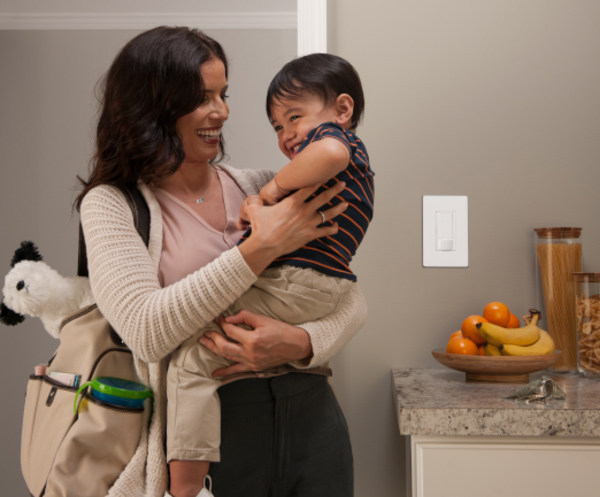 Mother holding child, with Caseta switch in the background
