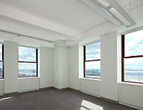 Corner office midday – bright daylight illuminates the space, lights automatically dim to minimum levels.